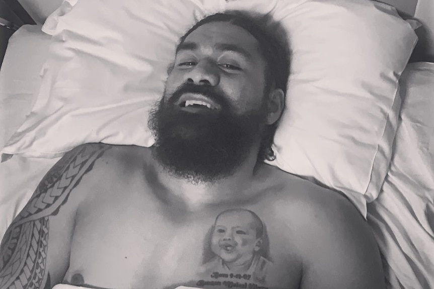 Former NRL player Mose Masoe lying in a hospital bed following his injury.