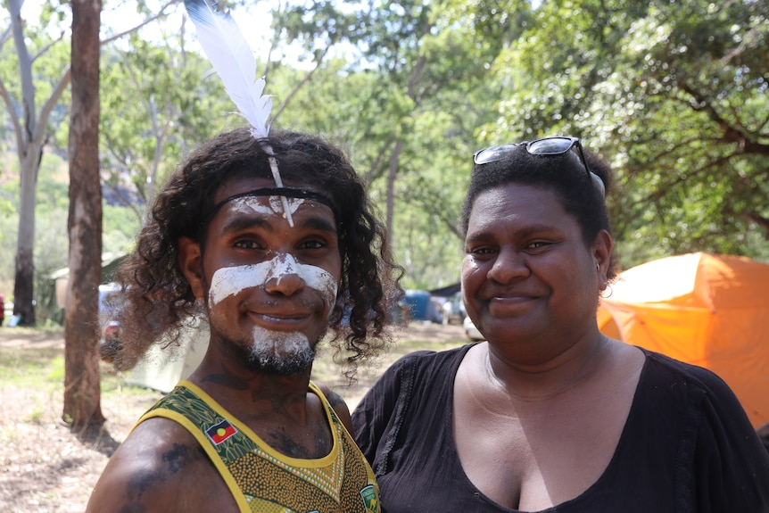 Close up portrait of a man who has a white feather and white face paint, and a woman wearing a black shirt.