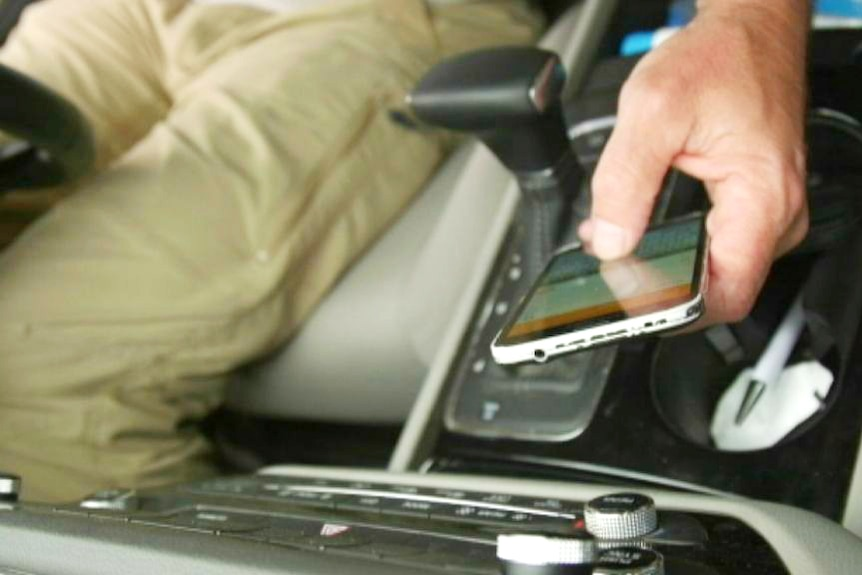 An unidentified person uses a mobile phone low near the gear changer in a car.