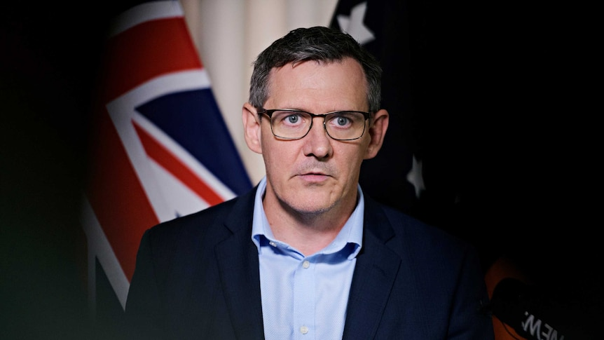 Chief Minister Michael Gunner is standing in front of a microphone with a serious expression. Behind him is the Australian flag.