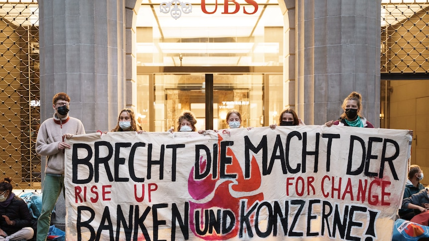 Six young people wearing face mask hold a white sign with German words on it in front of a bank building.