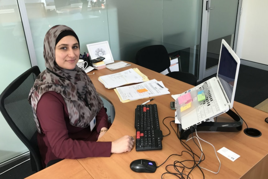 A smiling woman wearing a hijab sits at a tidy desk