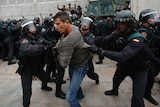 Three police in riot gear wrestle with a man.
