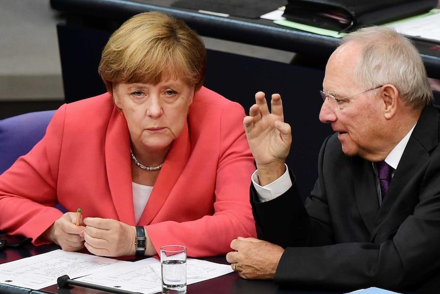 German chancellor Angela Merkel confers with finance minister Wolfgang Schaeuble