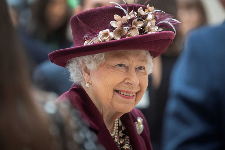 An elderly woman wearing a matching jacket and hat smiles as she talks with people.