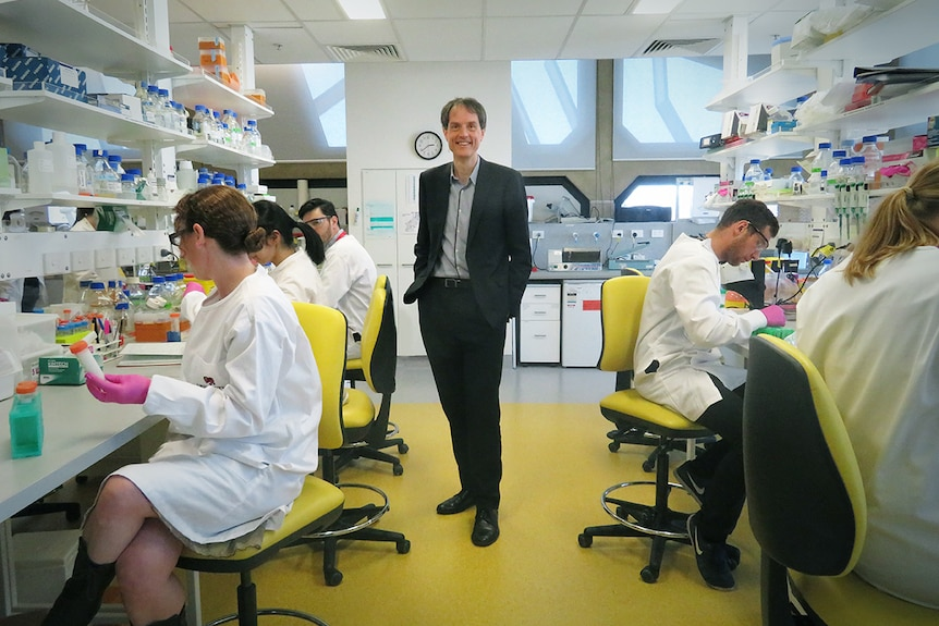 Rufus Black stands in centre of science lab, surrounded by students.