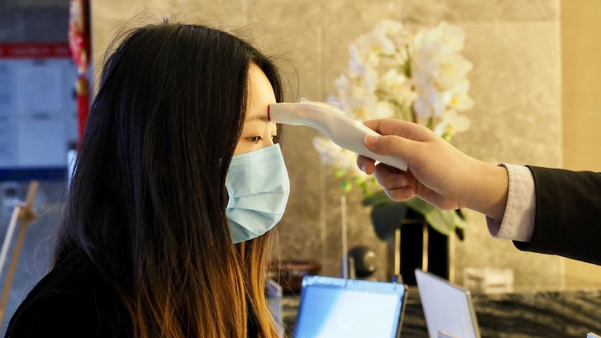 A hotel guest has a temperature measuring device placed on her forehead inside a hotel lobby