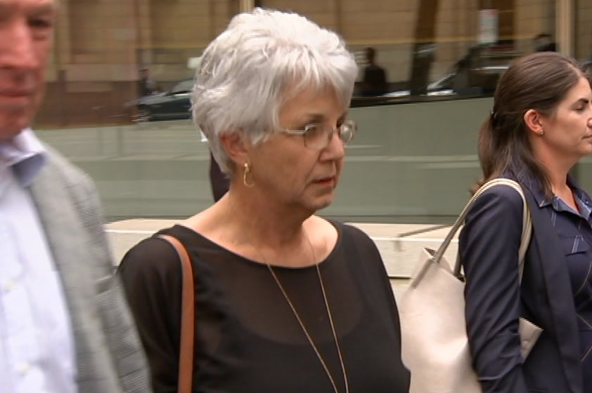 A woman with grey hair wearing a black top and glasses.