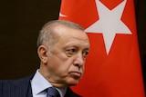 Turkish President Erdogan scowls near a Turkish flag.