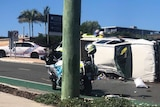 A damaged ute lies on its side with police vehicles around it.