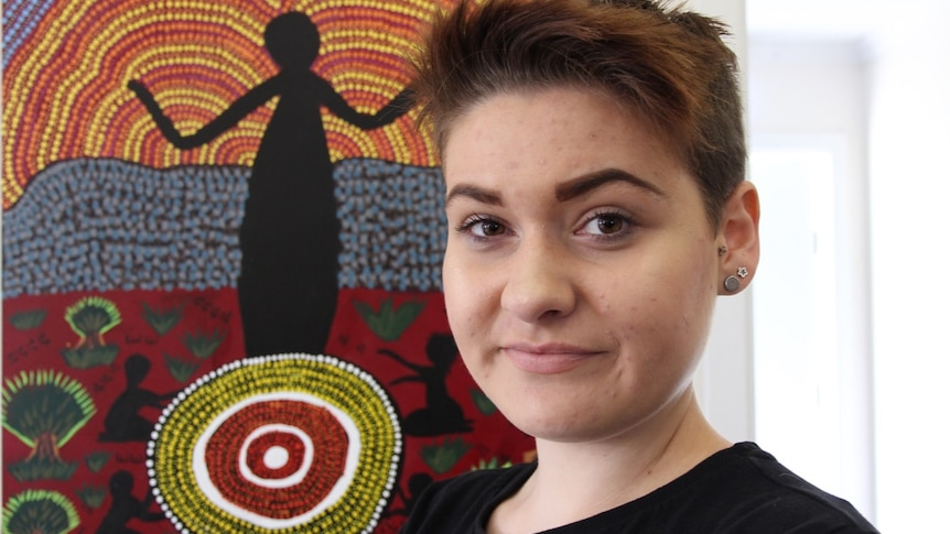A young woman, Jamira Pemberton, standing in front of her painting of a dreamtime story