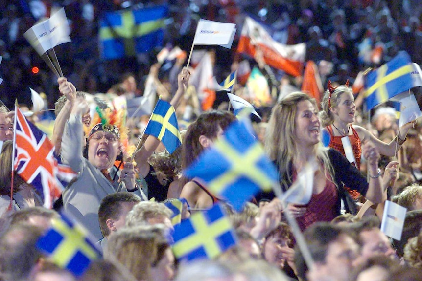 A cheering crowd wave mainly Swedish flags in the audience at the 2000 Eurovision Song Contest.