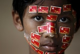 A boy places stickers with National League for Democracy (NLD) party logo on his face