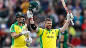 A batsman raises his helmet and bat in the air in celebration of an ODI century