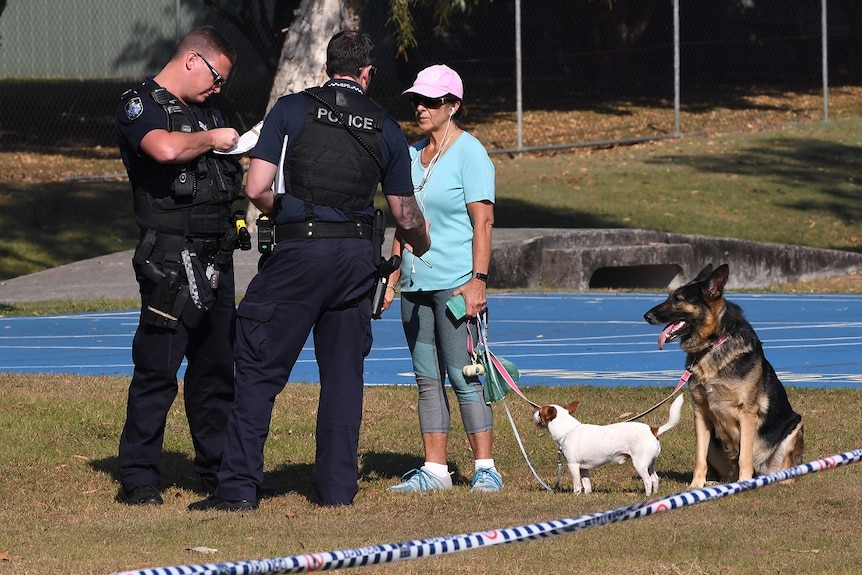 Police speak with a woman walking her dogs at a crime scene in Frascott Park,