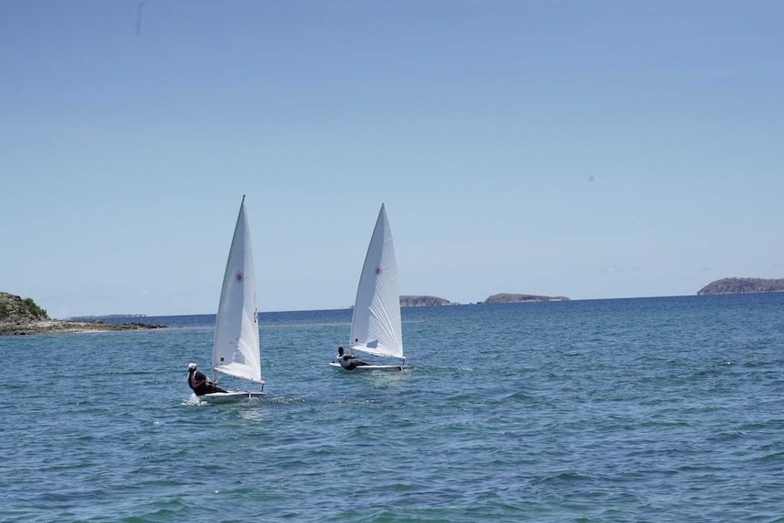 Two people on two boats sail on water with a clear sky above them.