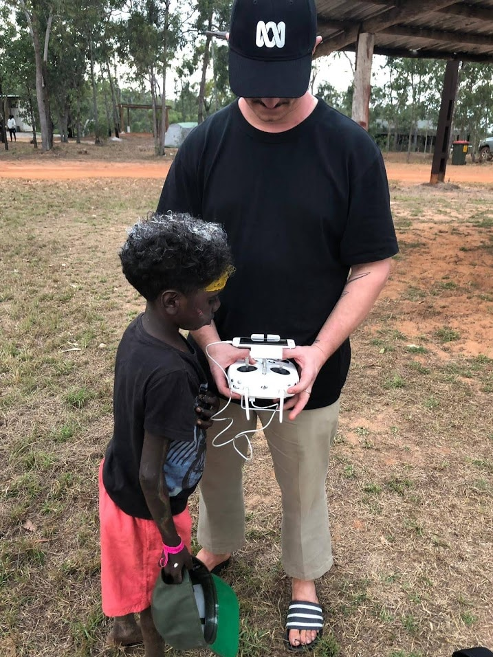 Man holding drone operating device showing young boy how it works.
