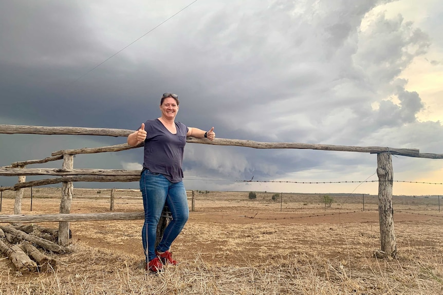 Woman standing in front of storm front and wooden fence