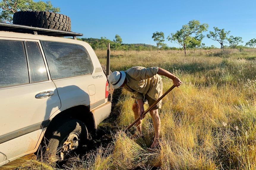 A man digs under the tyre of a white four-wheel-driver car in a grassy plain with trees in the background
