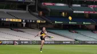 Dustin Martin kicks a ball at an empty MCG.