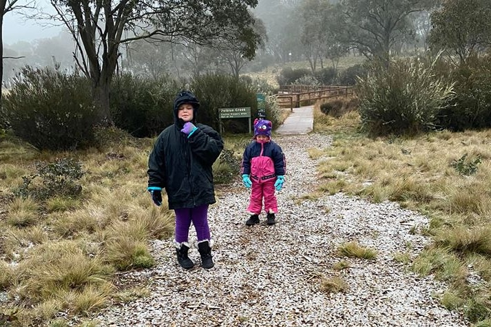 Two children in snow jackets stand on a walking track covered in snow.