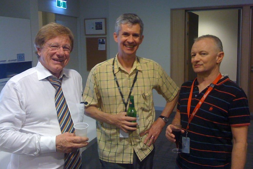 O'Brien, Napper and Green smiling to camera and holding drinks.