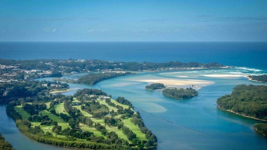 Aerial view of green coastal golf course surrounded by river
