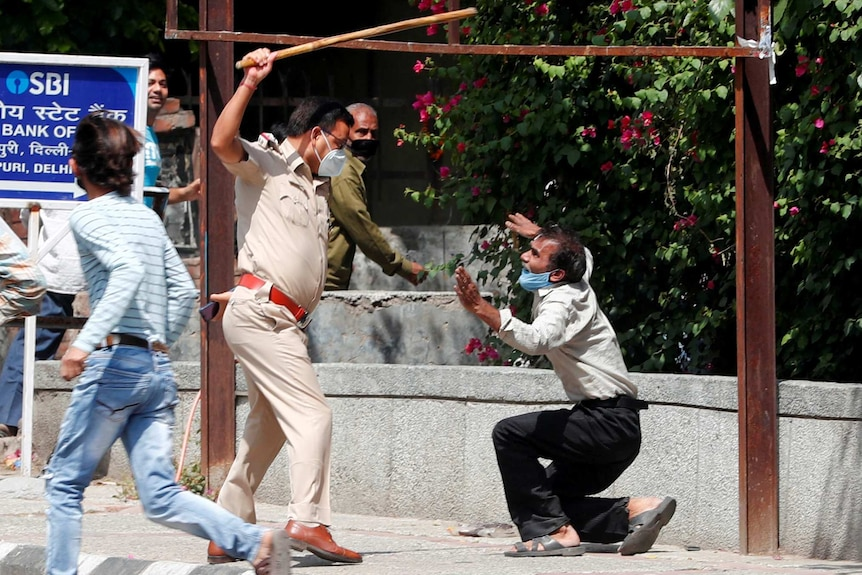 A police officer holds a cane above a crouching man in a face mask
