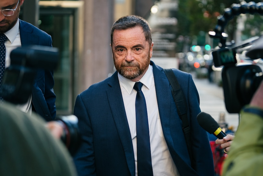 Michael wears a navy blue suit and tie with white shirt, walking down a city street with a media scrum surrounding him.