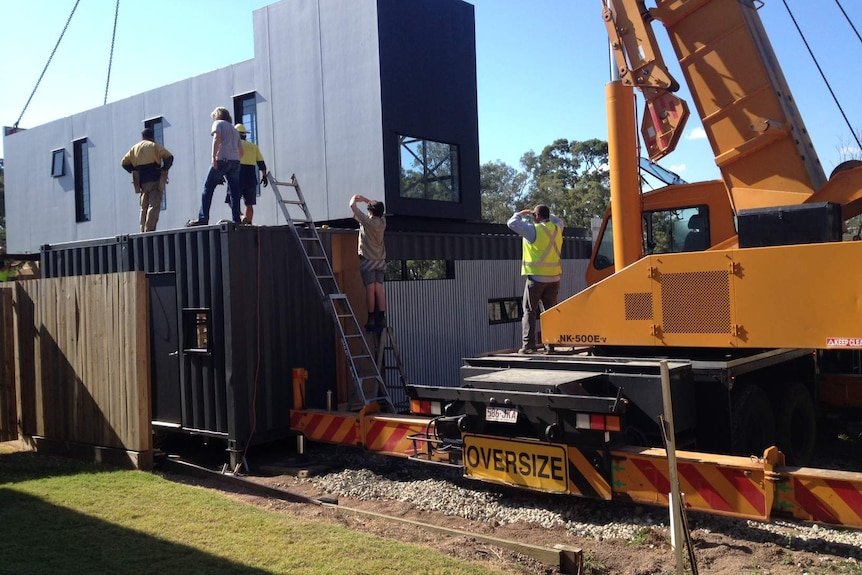 Construction workers putting together a home made out of shipping containers