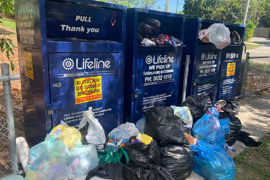 Four charity bins from Lifeline overflowing with donations and items strewn in front of them.