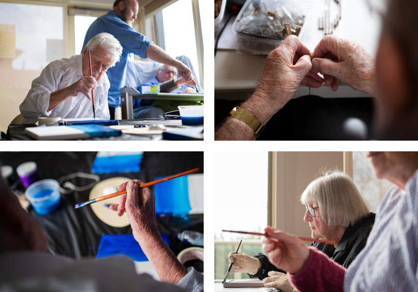 Elderly people paint at a craft session in an aged care facility