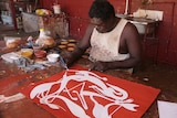 Artist and co-manager Gabriel Maralngurra paints in traditional ochre paints.