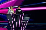 A blonde woman stands next to a brunette man. She wears a silver dress and he wears a black suit. They're at a podium.