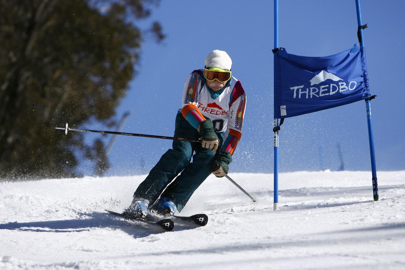 An elderly man skis downhill