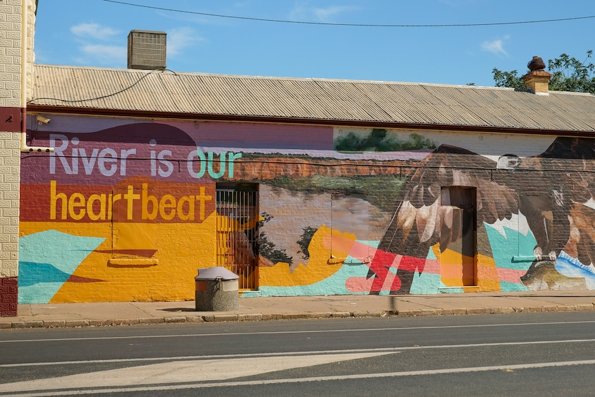 A brightly coloured mural on the side of a building at Wilcannia reads River is our heartbeat