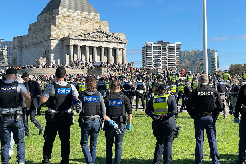 A ring of policemen and women stand
