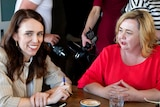 New Zealand Prime Minister Jacinda Ardern, left, and Megan Woods talk with colleagues at a cafe in Auckland, New Zealand.