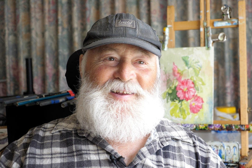 A 67-year-old man with a white beard and gentle smile sits in front of his painting of pink flowers