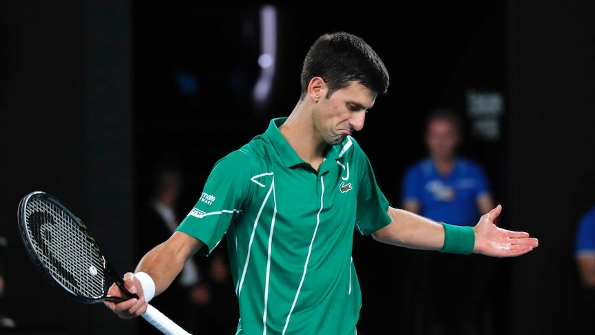 A tennis player spreads his arms wide after losing a point.