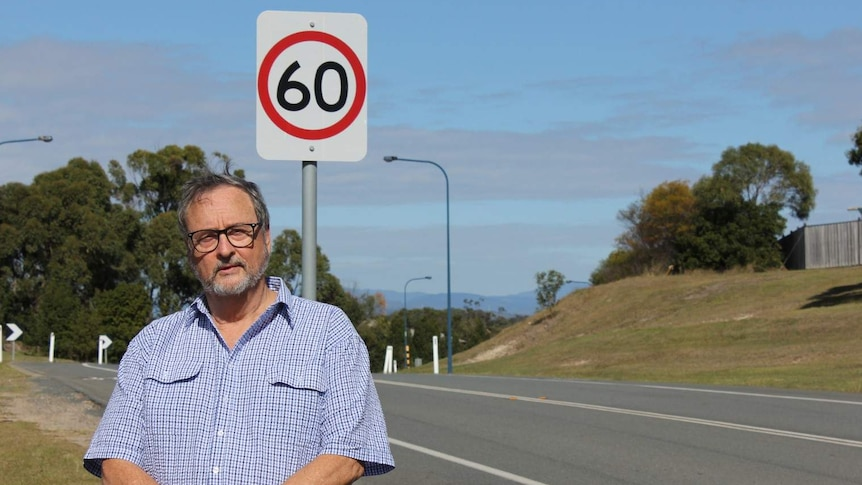 Resident Michael Malone standing in front of a 60km/h speed limit on Colman Road, a hooning hotspot.