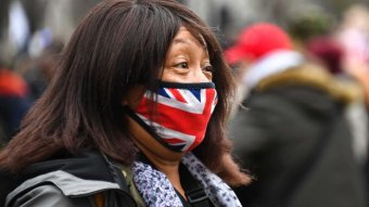 A woman wears a face mask with the UK flag printed on