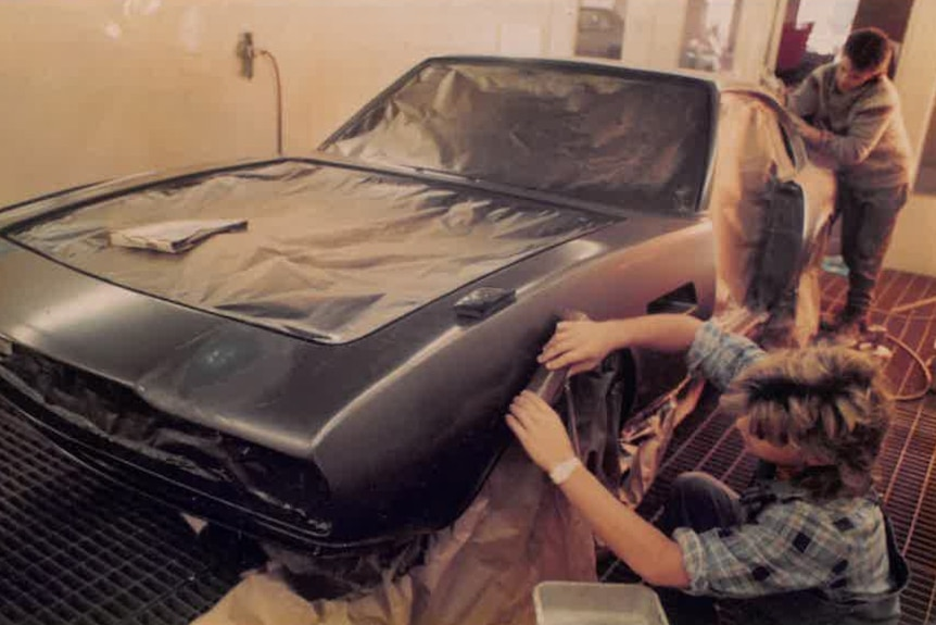 Two young men work on the body of a car, restoring the paint