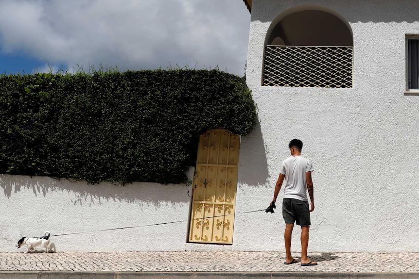 Man walks dog next to white apartment building