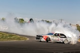 Car white car drifting with smoking tyres on a race track