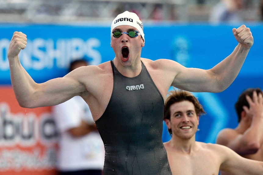 Paul Biedermann wears a black swimming suit that covers his torso and clenches his fists with his mouth open