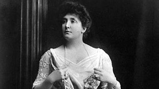 Black and white photo of Dame Nellie Melba standing holding a long pearl necklace.