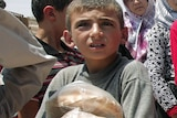 A Syrian boy carries bags of bread as people queue up outside a bakery in the northern town of Aldana