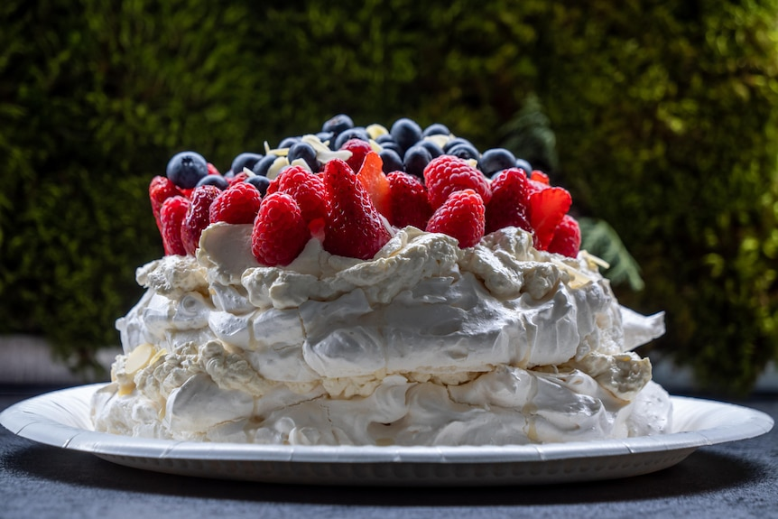 A pavlova topped with assorted fruit