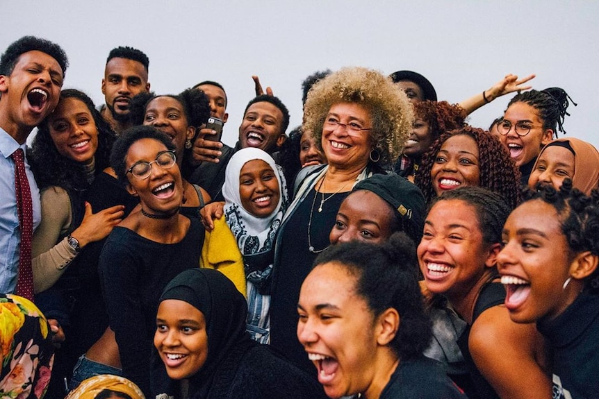 A group of young black people surrounding the activist and academic Angela Davis, everyone is smiling
